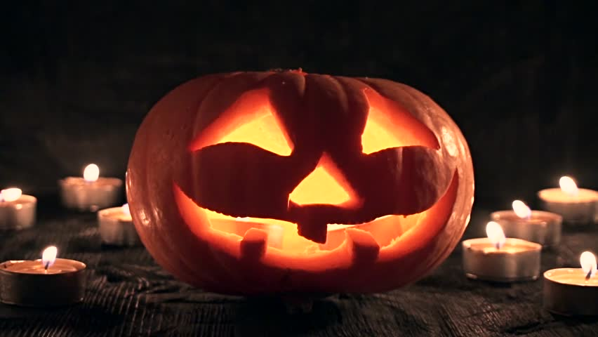 Carved Halloween pumpkin lights inside with flame on a black background with lighted candles close up. slowmotion | Shutterstock HD Video #18401140