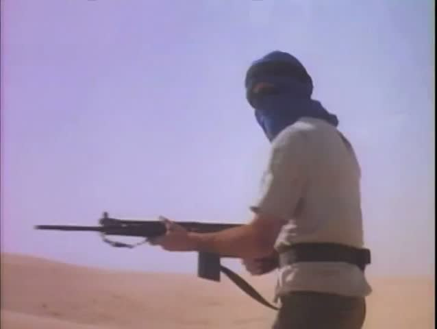 Man in turban firing machine gun