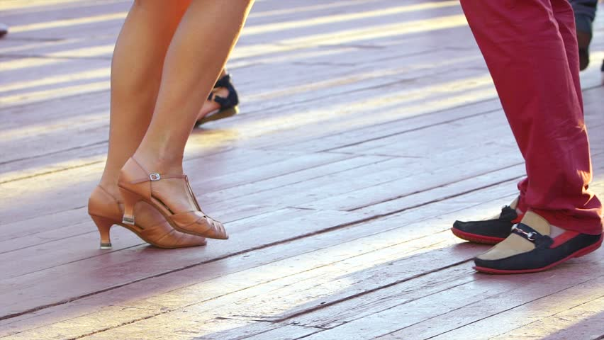 Couples perform Latin dances in the street. Close-up of feet of a dancing  couple.