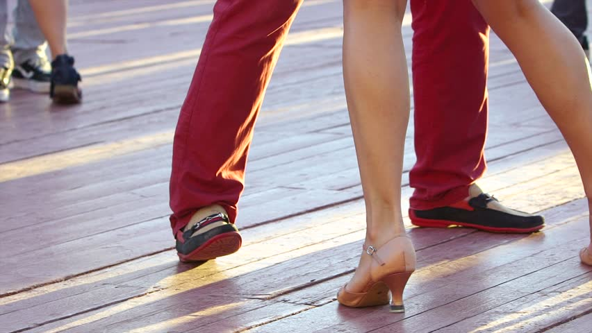 Couple perform Latin dances in the street. Close-up of feet of a dancing