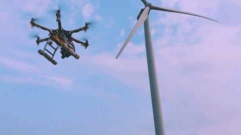 Drone flies near the wind turbine, slow motion.