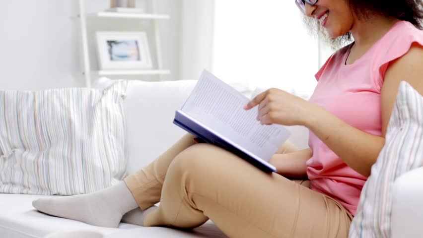 Leisure, literature and people concept - smiling african american young woman in eyeglasses reading book at home | Shutterstock HD Video #18492880