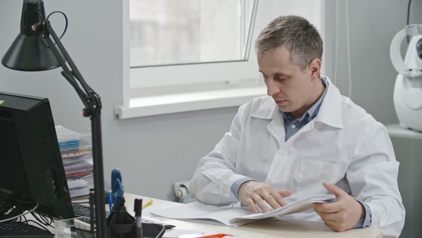 Doctor in white medical gown sitting at desk in his office, looking through medical records and making notes
