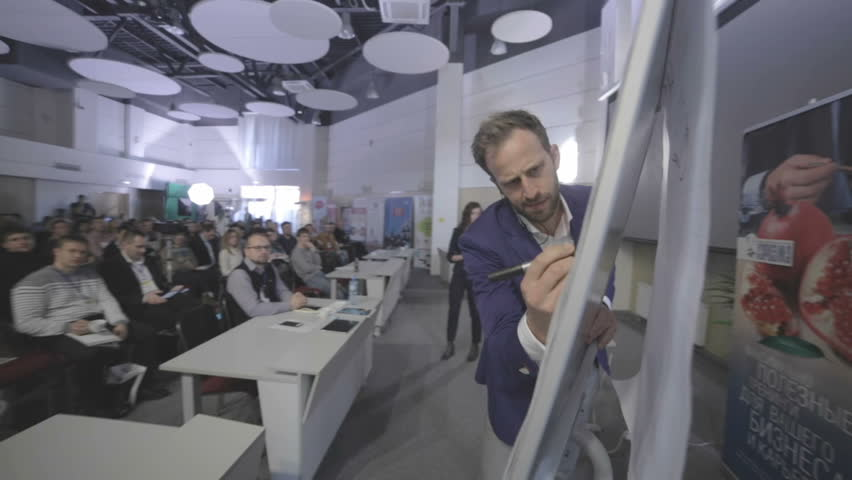Russia, Novosibirsk, November 2014: Lecturer standing in front of an audience near a flip-chart. The lecturer writes marker on the flip chart. Emotional speaker makes a report. Lecturer stands in | Shutterstock HD Video #18504080