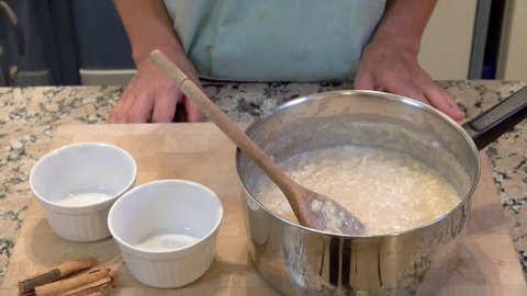 Woman serving homemade arroz con leche, rice pudding