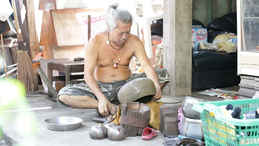 BANGKOK - NOVEMBER 12: A man shapes an alms bowl in Bangkok, Thailand on November 12, 2011. Alms bowls are used by monks during their morning processions.