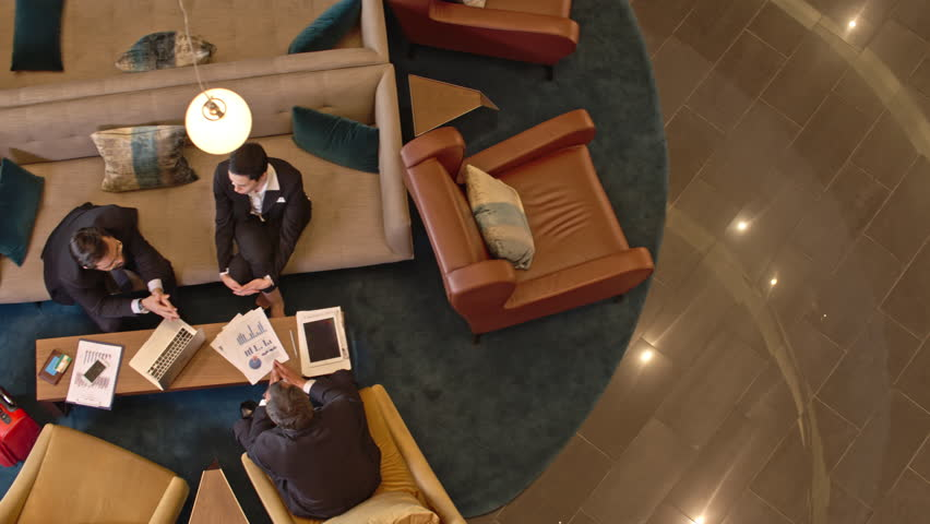 Directly above view of businessmen and businesswoman sitting in the hotel lobby and sharing ideas