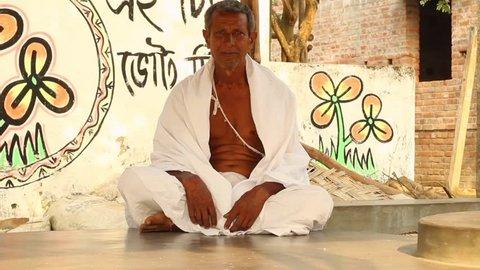 Brahmana priest sitting on a platform in a village in Bengal, India. Tilt shot