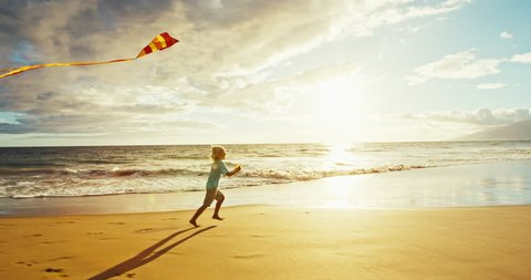 Young boy playing with kite on the beach