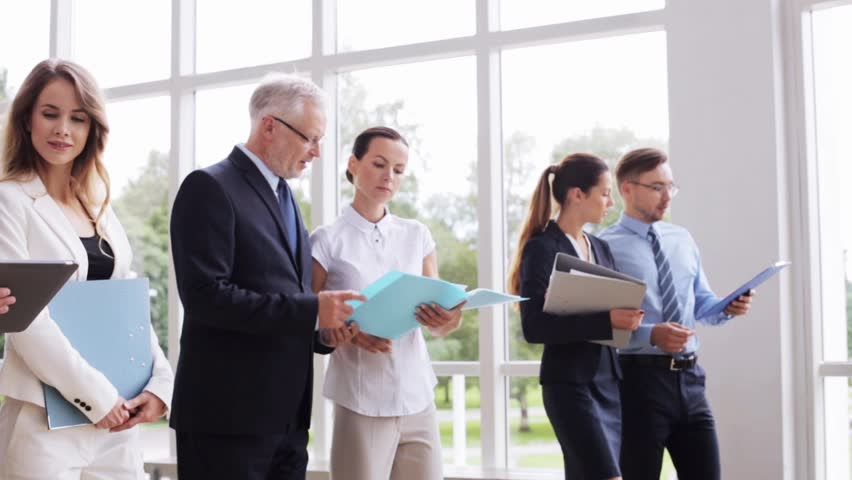 People, work and corporate concept - business team with folders and tablet pc computer walking along office building and talking | Shutterstock HD Video #18607250