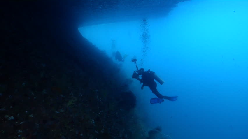 Distant group of scuba divers swimming in overhang in Indonesia, HD, UP23819 | Shutterstock HD Video #18620870