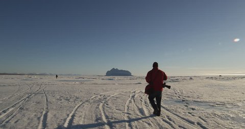 Photographer walks across snow sea ice to ice hill on sunny day in the arctic - A026 C005 0617XF 001