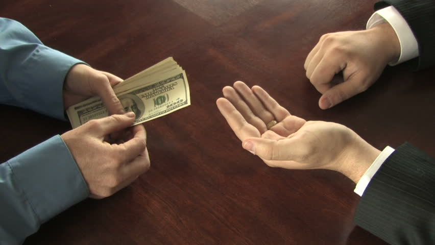 A man counts out hundred dollar bills into the hand of another businessman, who takes the money