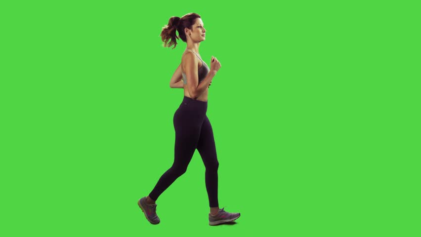 Young woman running over green screen, wearing a sport bra, smiles.