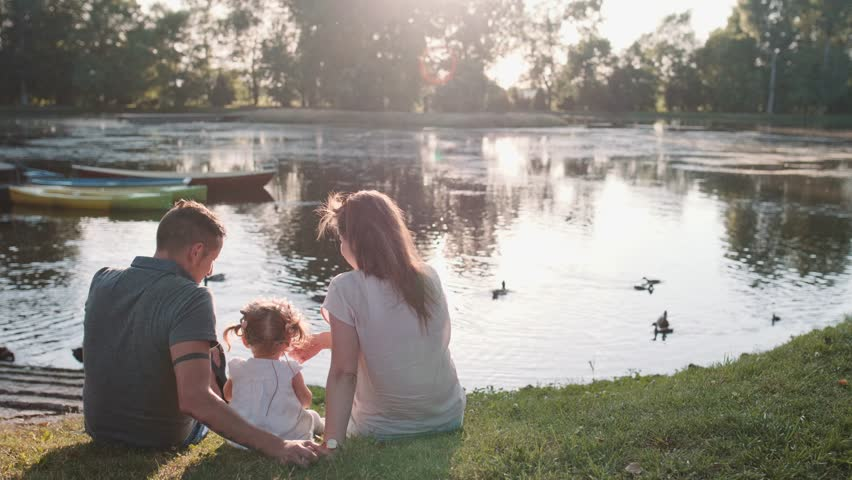 Young family with Baby Girl Enjoying Sunny evening in the Park. Slow Motion 120 fps, 4K. Parents relaxing with their toddler daughter near lake. Happy childhood and Parenthood. Love and Happiness