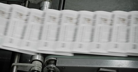 Tomorrow's newspapers are moved through the factory on conveyor belts. (2010s)