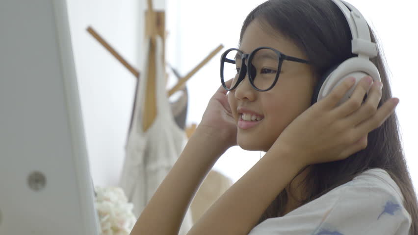 4K : Attractive Asian girl listening music on computer with headphone in the room, Pan shot | Shutterstock HD Video #18691100