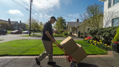 Senior adult delivery man with severe back pain impatiently tosses packages onto front porch of an American suburban home