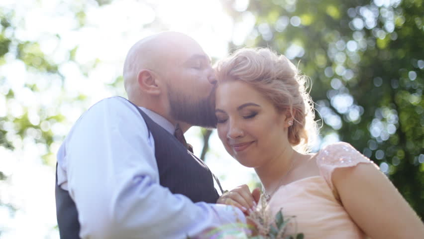 Sensual close up portrait of handsome groom kissing forehead of his beautiful bride, outdoors | Shutterstock HD Video #18717290