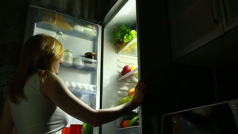 Woman opens the refrigerator at night. night hunger. diet. gluttony