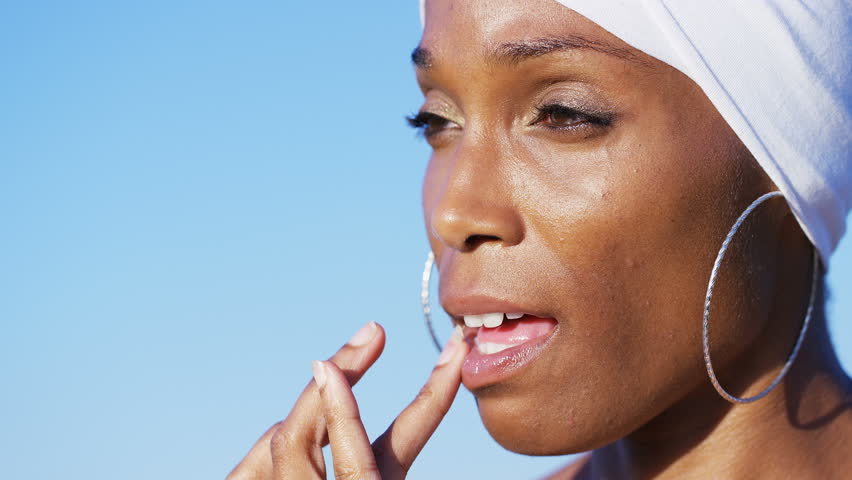 4K Attractive african american woman applying lip balm to her lips, in slow motion