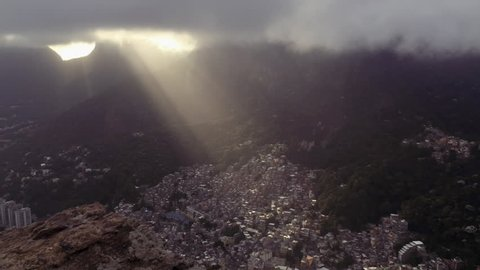 Shafts of sunlight shine through timelapse clouds moving over the crowded Brazilian Rocinha favela shanty town in Rio de Janeiro, Brazil