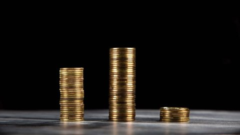 Growing stacks of coins on black background, stop motion video