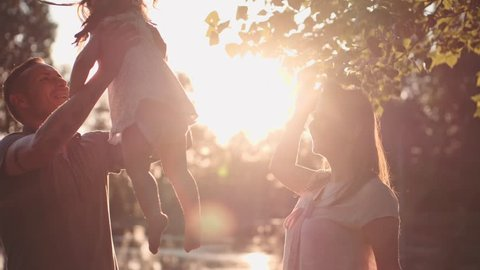 Young family with Baby Girl Enjoying Sunny evening in the Park. Slow Motion 120 fps, 4K. Parents playing with their toddler daughter near lake. Happy childhood and Parenthood. Love and Happiness