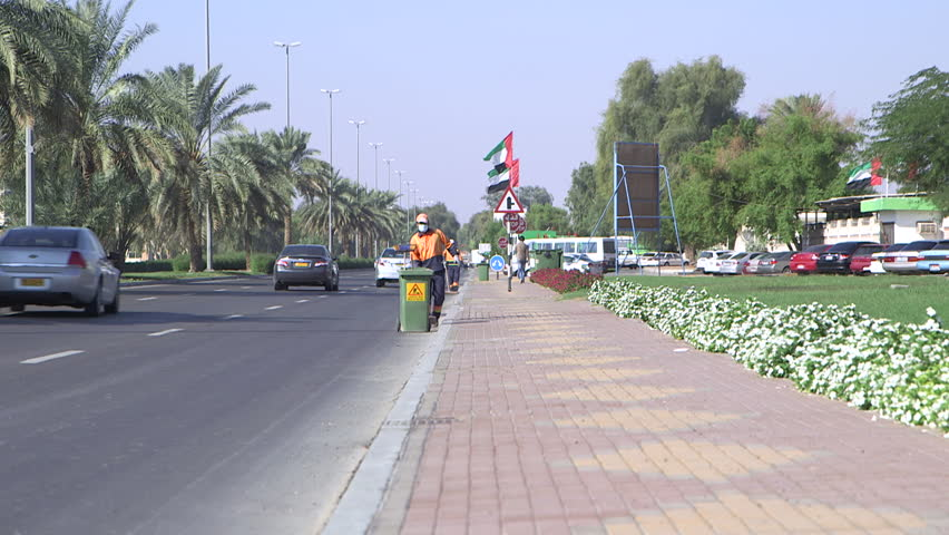Abu Dhabi, UAE - Wide of a two men wearing face masks sweeping litter from the side of a landscaped road in Abu Dhabi. (Abu Dhabi, UAE-2013)