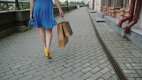 legs slender young woman, walking in the city past the store with shopping bags, back view, slow mo, stedicam shot