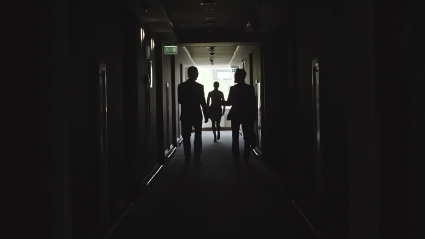 Dark silhouettes of two businessmen walking in the corridor of dark silhouettes of two businessmen walking in the corridor of office center while woman running behind and trying to catch them stock footage video sciox Images