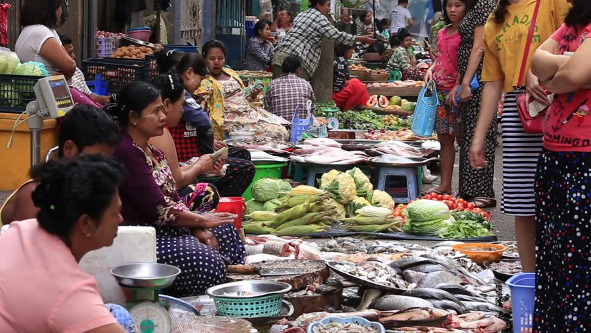 YANGON, MYANMAR - JANUARY 10, 2016: Unidentified people buy and sell seafood and vegetable on the street food market in the city center