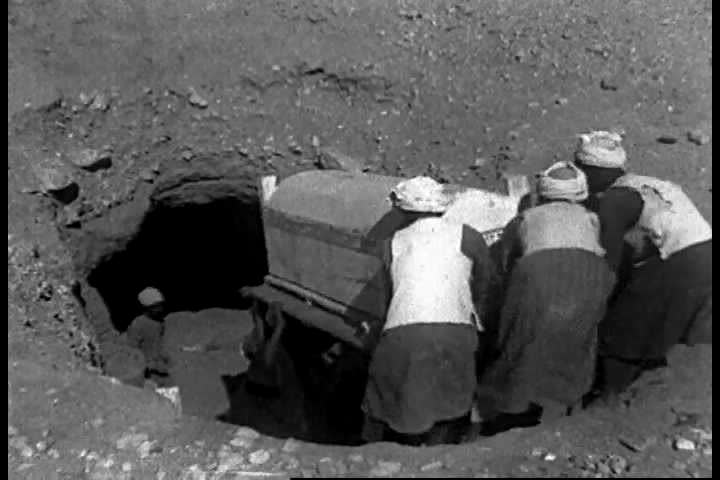 Coffins are removed and transported by laborers from a thousand year old crypt at Deir el Bahri, Egypt in the 1920s. (1920s)