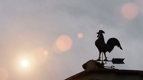 Weather vane in rooster shape on the roof, sun raising.Time lapse, lens flare