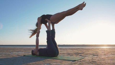 beautiful couple doing acro yoga on the beach, slow motion