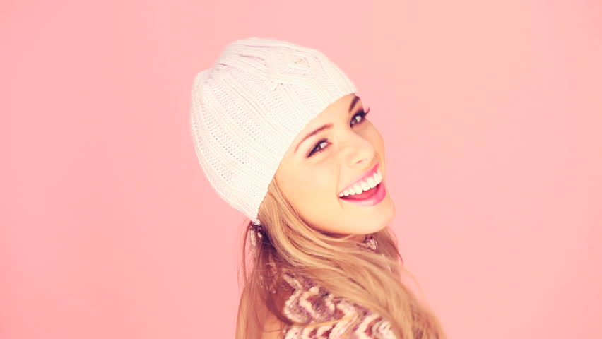 Seductive Blond In Winter Outfit with beautiful smile facing out of frame with copyspace on pink.