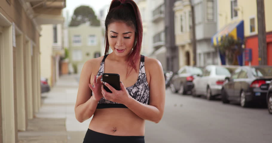 Japanese woman jogger using phone in the city | Shutterstock HD Video #18920810