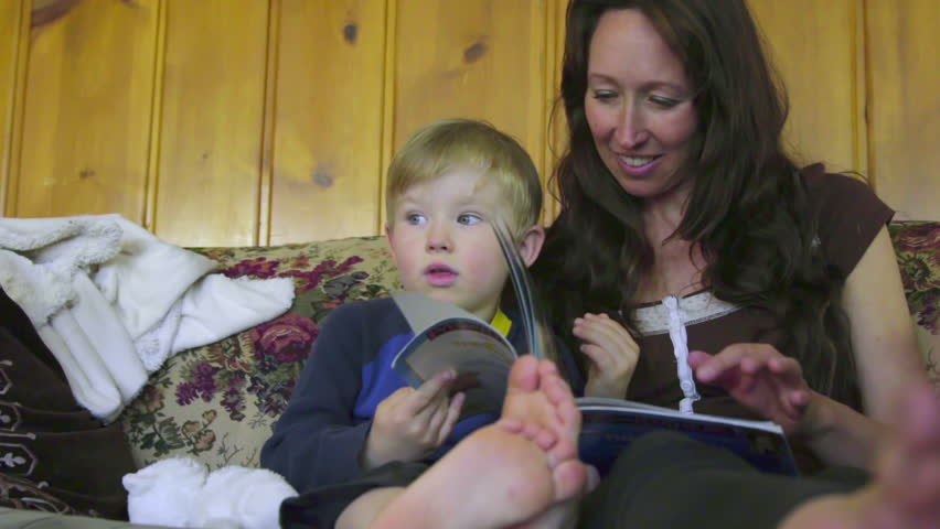 Mother and son read a book on the living room couch when the child decides to get up and leaves