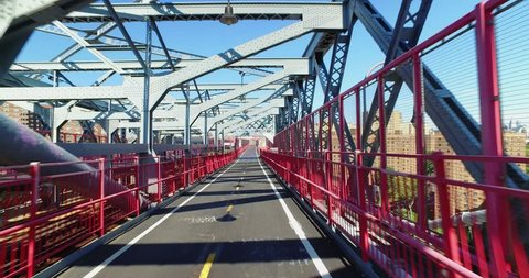 A personal perspective view walking or riding on the pedestrian sidewalk portion of the Williamsburg Bridge over the East River between Manhattan and Brooklyn.