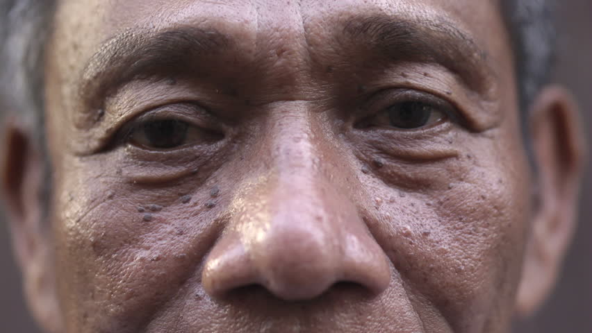 Depression and sadness of depressed and sad mature asian man looking at camera. Extreme close-up of eyes and face