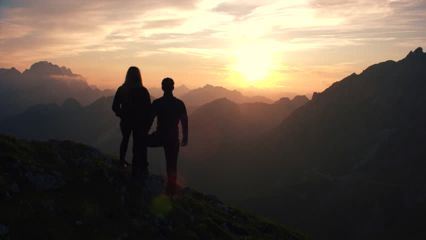 Aerial, edited - Raising above hiking couple watching beautiful sunset in the mountains | Shutterstock HD Video #18955580