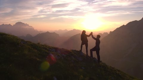 Aerial - Flyover hiking couple celebrating successful climb on the mountain with a high five at sunset