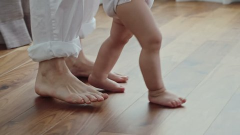 Side view of barefoot legs of woman walking on the floor behind little baby in diaper