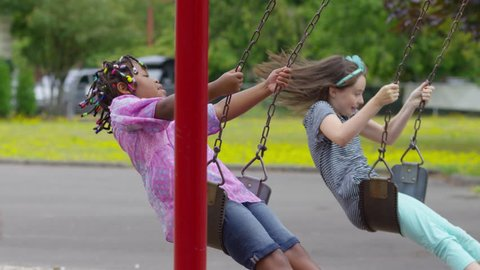 Students swing on school playground, slow motion