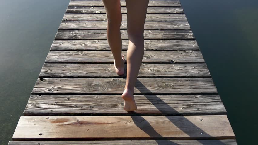 Woman walks on wooden pier in a summer day after jogging and dives into the water, slow motion
