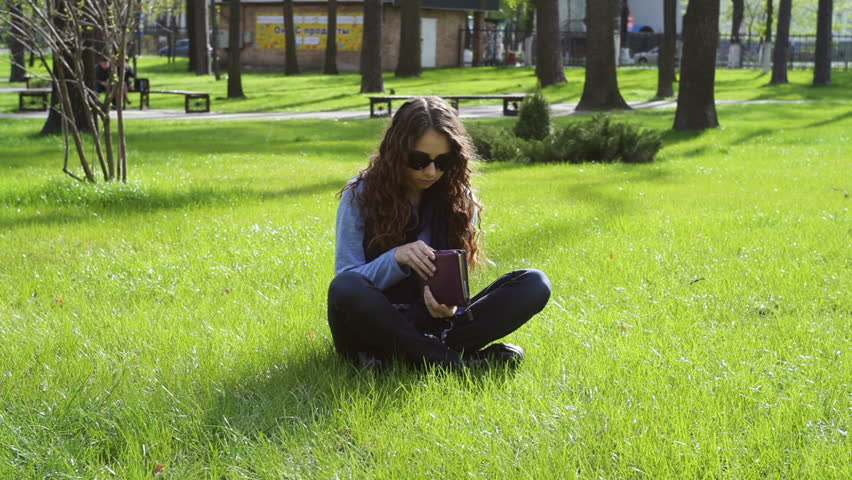 Beautiful young woman sitting in the park on the grass and reading a book | Shutterstock HD Video #19008880