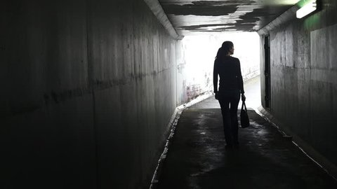 Silhouette of a man thief ambush steals a bag from a woman in a dark tunnel. Violence against women concept. Real people, copy space