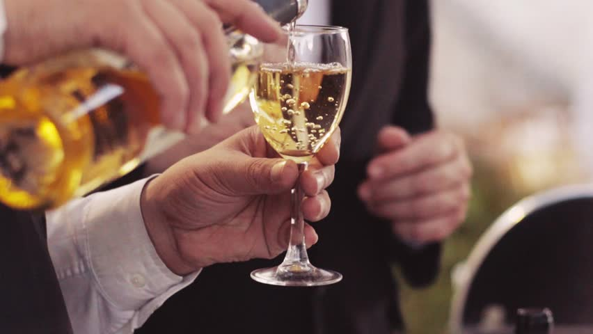 A waiter is pouring white wine into the wineglass. Male portrait, outside shooting. Wine bubbles. Wedding party. Italian wine. Close up view, slow motion.