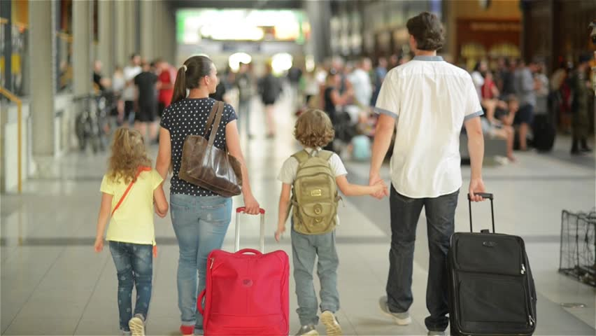 Happy family with little girl and boy going on railway station, mother father and the kids walk through the airport with suitcases | Shutterstock HD Video #19038394