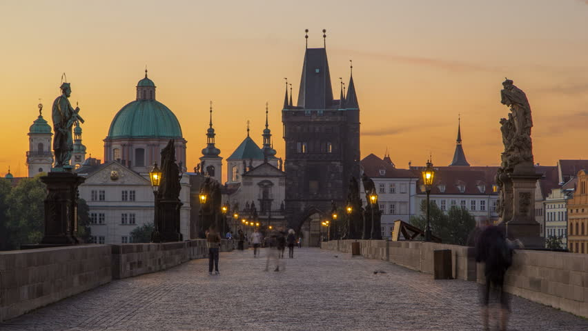 Charles Bridge in Prague before the sunrise night to day transition timelapse, Bohemia, Czech Republic. Orange sky